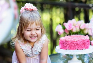 happy little girl with pink cake, roses, and trees in the background