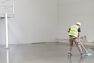 a person cleaning concrete floors
