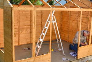 Man constructing a wooden shed