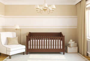 A wooden crib in a neutral baby room.