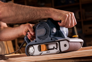 smoothing wood plank with electric sander