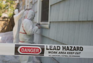 A tape with a lead hazard warning on it against a house.