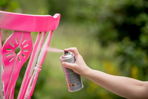 Someone spray painting a wood chair in the color hot pink.