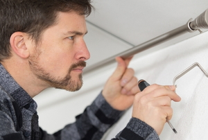 man installing a bracket support for a curtain rod