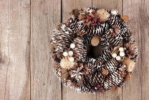 A rustic pine cone wreath against a wood background.