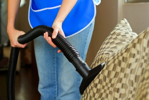 A person cleaning a sofa with a vacuum cleaner.