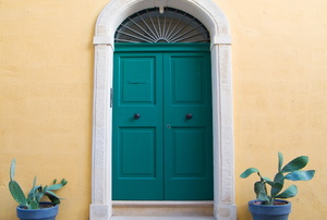 A green door with a marble threshold.