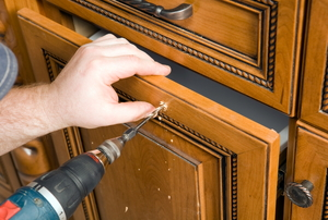 cabinet being repaired with a drill