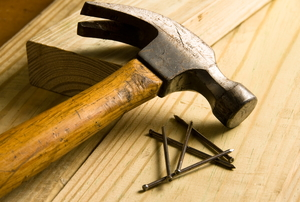 A hammer and nails sitting atop lumber pieces.