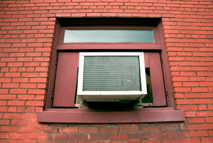 A window air conditioning unit installed in the window of a brick building.