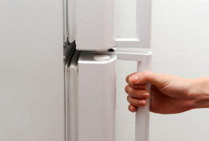 A hand on a white fridge door handle.