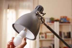 a lamp with someone putting in a lightbulb