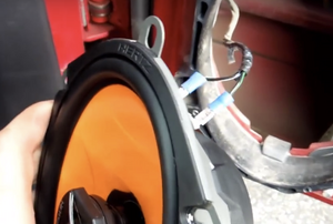 A car speaker pulled out to expose the wiring.