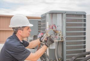 An HVAC technician replacing an AC capacitor.