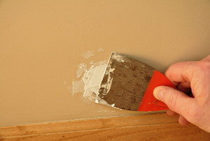 Covering a hole in the drywall with spackle.