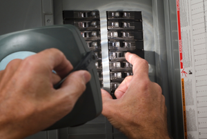 man flipping a breaker in a circuit panel