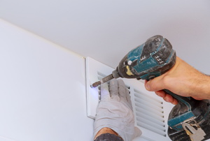 A man installs an exhaust fan.