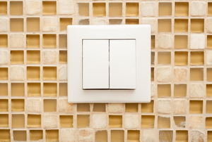 light switch with tiled wall behind it