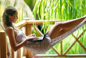 A young woman working on her laptop in a hammock