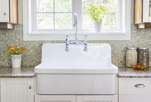 A white kitchen sink in front of a window with a beige interior.