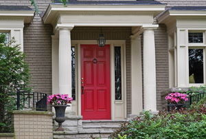 A front porch to a house with a red door.