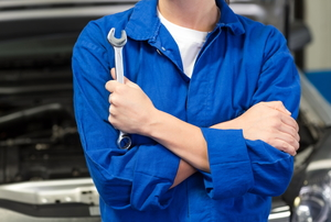 mechanic holding wrench in front of a car