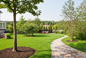 A landscaped space with grass, trees, and a paved path.