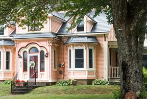 pink painted Victorian house with lawn and tree