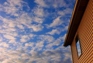 The side of a house and the cloudy sky above.