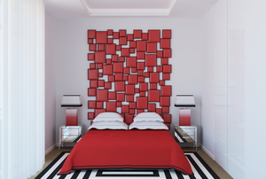 Bedroom with red bedspread and red wall art as a headboard