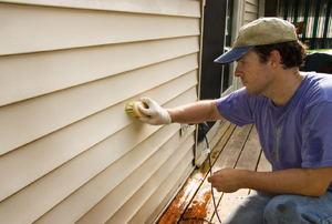 A man installs siding.
