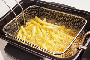 French fries in an electric deep fryer basket.