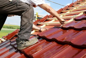 A man climbs on a fiberglas roof.