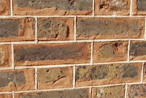 tuckpointing brick wall with multicolored mortar