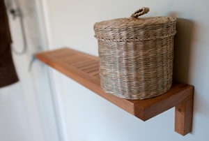 A wicker basket with a lid on a narrow timber shelf in a bathroom.