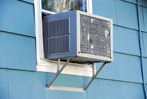 A window air conditioning unit in a blue house.