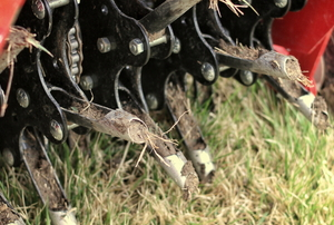 A mechanical aerator pokes holes in a lawn.