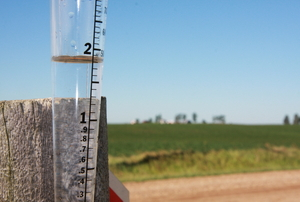 A simple rain gauge attached to a fence post on a rural farm.