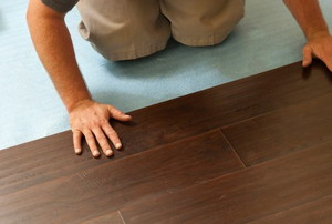 person installing floating laminate flooring