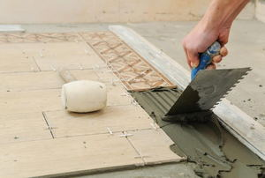 A diy-er measuring tile with a ruler and pencil.