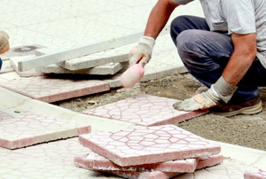 person installing rubber pavers