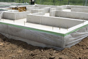 A concrete slab foundation with houses in the background.