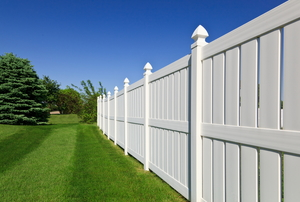 A white vinyl fence next to a newly-mowed yard.