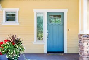 A blue exterior door leading onto a concrete patio.