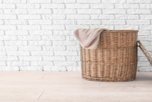 A laundry basket against a white brick wall.