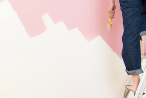 Someone standing on a ladder painting a wall pink.