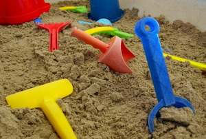 A sandbox full of plastic shovels and buckets.