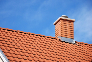 A red tiled roof with a brick chimney, topped with a chimney cap.