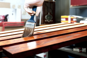 Someone applying varnish onto wooden planks.