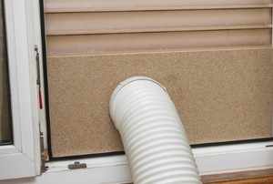 A portable AC exhaust hose fed through a window covering.